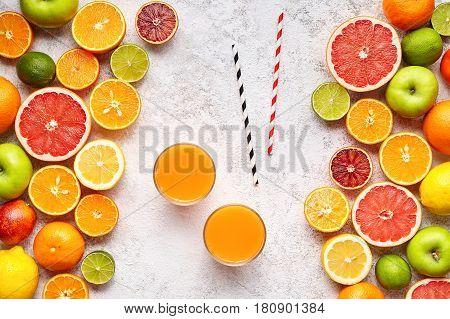 Smoothie or fresh juice vitamin c drink in citrus fruits background flat lay, healthy lifestyle vegetarian organic antioxidant detox diet beverage. Tropical summer assortment grapefruit, orange, apple