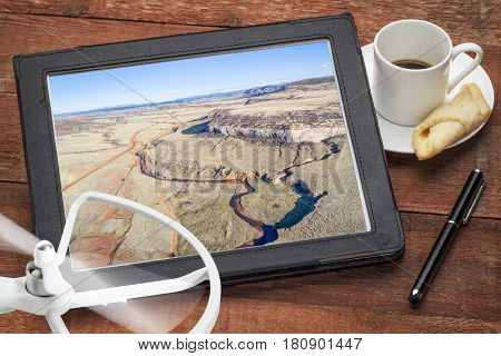 aerial photography concept - reviewing pictures of Colorado foothills with a stream and cliff on a digital tablet with a drone rotor and coffee, screen picture copyright by the photographer