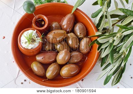 Olives in a traditional brown ceramic bowl, with tzatziki sauce, lemon, garlic, olive branch and olive oil on a white abstract background.