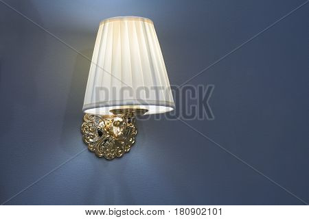 Old style metal switched on lamp mounted on blue wall with lampshade