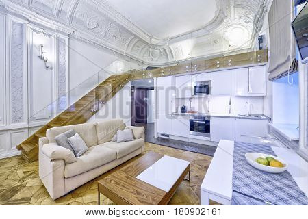 Classic interior design duplex apartment with white wall and ceiling moldings.Russia, Moscow region - interior design kitchen - living room.