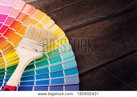 paintbrush on colorful paint swatches with copy space
