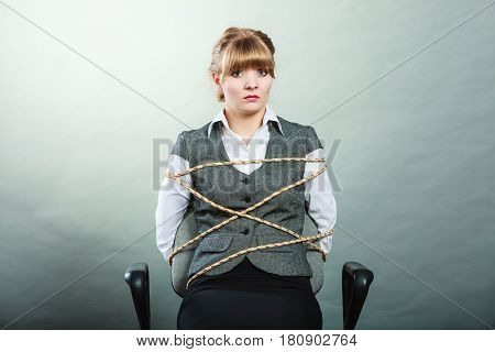 Afraid kidnapped businesswoman tied with rope to chair. Woman kept prisoner. Girl being imprisoned incarcerated.