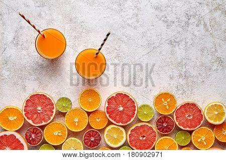 Fresh juice or smoothie vitamin c drink in citrus fruits background flat lay, healthy lifestyle natural organic antioxidant detox diet beverage. Tropical summer assortment grapefruit, orange, apple
