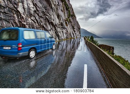Wet road after rain with blue car in Norway. Car driving safety concept.