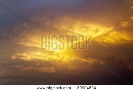 Beautiful dark fluffy cloudy sky with sun rays. Cloudy abstract background. Sunset light.