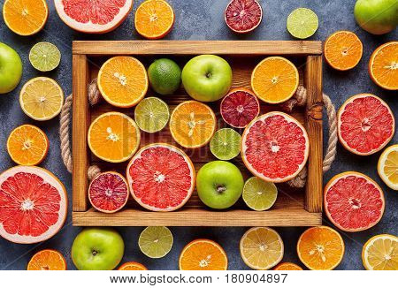 Different citrus fruit on a wooden box and grey concrete table. Fruit food background.Antioxidant, detox, dieting, clean eating, vegetarian, vegan, fitness or healthy lifestyle concept. Flat lay.