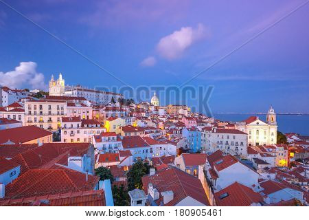 View of Alfama, the oldest district of the Old Town, with Monastery of Sao Vicente de Fora, Church of Saint Stephen and National Pantheon during evening blue hour, Lisbon, Portugal