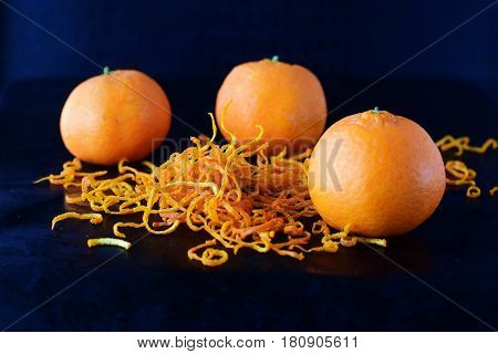 Fresh mandarine zest with full fruits on a dark blue abstract background.