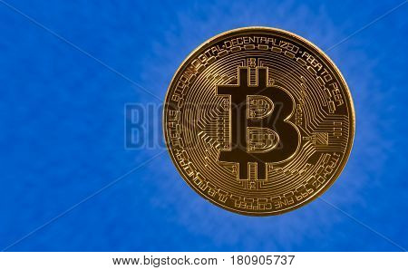 Single bit coin or bitcoin on blue cloud background to illustrate blockchain and cyber currency