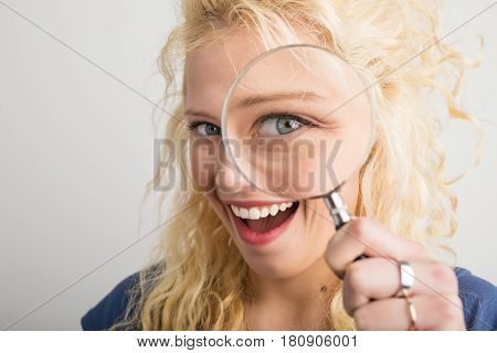 Woman looking through magnifying glass and smiling