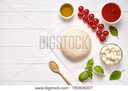 Raw pizza dough with baking ingredients: dough, mozzarella, tomatoes sauce, basil, olive oil, cheese, spices. Italian margherita preparation on white wooden table. Italian pizza margarita