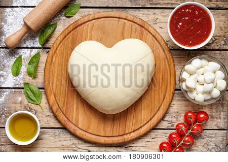 Pizza cooking ingredients. Cooking with love. Dough in heart shape. Baking ingredients on the wooden table: dough, mozzarella, tomatoes sauce, basil, olive oil. Italian food cuisine background.