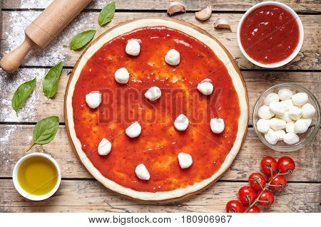 Pizza cooking preparation. Baking ingredients on the wooden table: dough, mozzarella, tomatoes sauce, basil, olive oil, tomatoes, cheese, spices. Italian food cuisine background pizza margherita