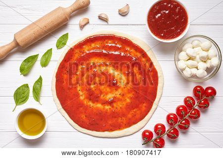 Pizza margherita cooking preparation. Raw pizza dough with baking ingredients: tomatoes sauce, mozzarella, basil, olive oil, cheese, spices. Italian food cuisine background. Flat lay.