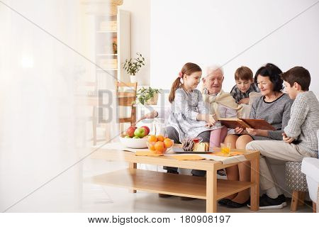 Grandparents Showing Photo Album To Their Grandchildren