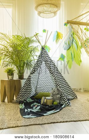 Unisex kids room interior with a tent in the middle