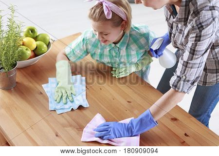 Mother And Daughter Wiping A Table