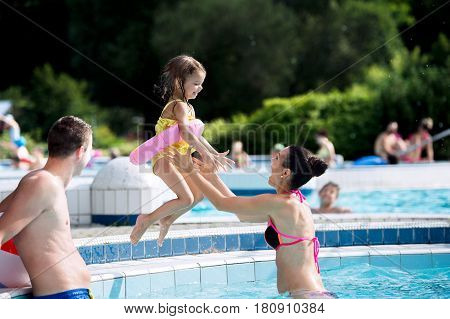 Young mother and father with their daughter in inflatable ring in swimming pool in aqua park, girl jumping into the water. Summer heat and water.