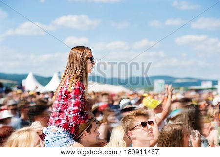 Teenage couple at summer music festival under the stage in a crowd enjoying themselves. Handsome man giving beautiful young woman piggyback.