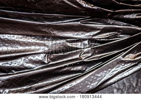 Close-up fragment of a crumpled black polyethylene trash bag's surface as a backdrop texture composition