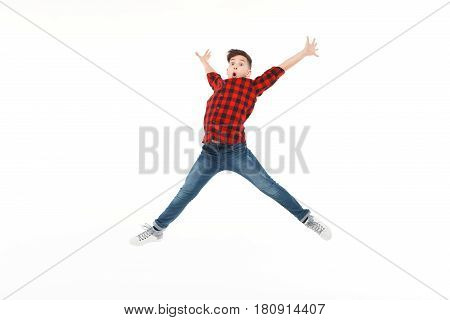 Expressive excited teenager in casual outfit in moment of jumping high on white .