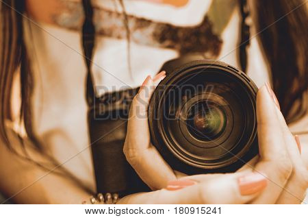 SLR camera lens in girl female hand