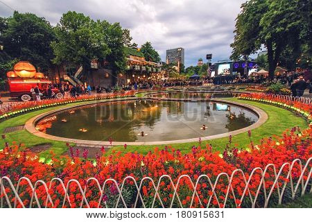 COPENHAGEN DENMARK - JUNE 15: Evening view of Tivoli Gardens with pond and concert hall in 2012