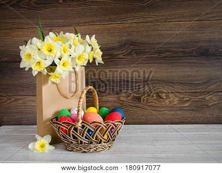 Colorful easter eggs in the basket with lovely bouquet of narcissus in paper bag on wood background