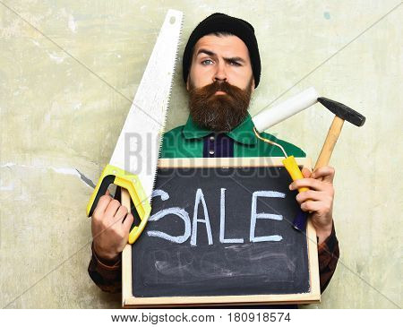 bearded man long beard brutal caucasian hipster with moustache holding various building tools: saw hammer roller paint and board with inscription sale with serious face on studio wall background