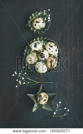 Quail eggs in metal molds and dried flowers for Easter holiday over dark scorched wooden background, top view