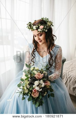 Young beautiful bride in a beautiful wedding gown with flowers. Wedding. Bride's morning.