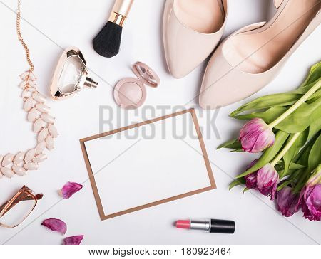 Stylish feminine accessories of beige color and blank paper with place for text or image. Trendy mock-up, top view
