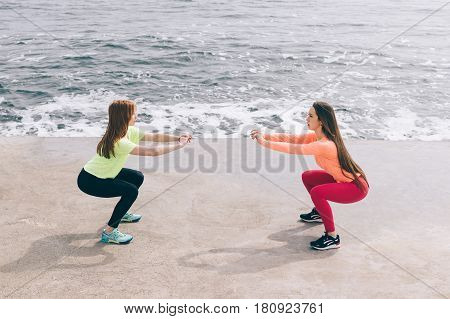 Two Sports Girls Doing Squats On The Beach.