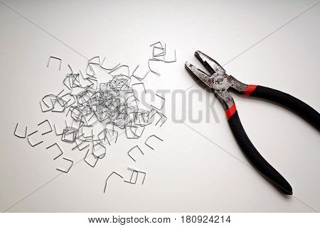 Pliers and staples for furniture on a white table isolated
