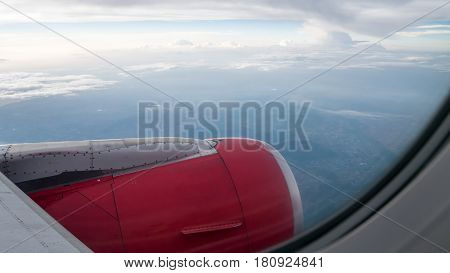 The engine cowling of airplane on the beautiful cloudy and sky view from airplane window.