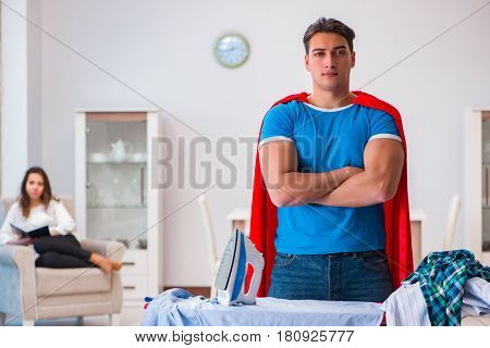 Super hero man husband ironing at home helping his wife
