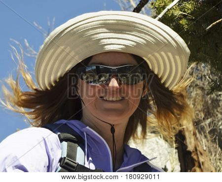 A Smiling Woman Hiking with the Wind Blowing Her Hair