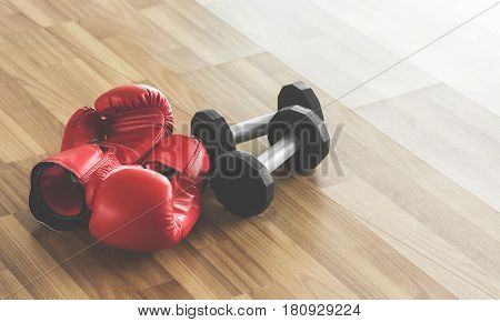 Red boxing gloves with dumbbells on wooden floor. Copy space.