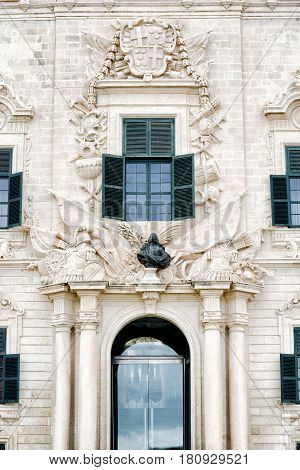 Auberge de Castille main entrance flanked by columns which support a trophy of arms and a bronze bust of Grand Master Manuel Pinto da Fonseca. Above is a moulded window surmounted by Pinto's coat of arms. December 19 2016 - Valletta Malta