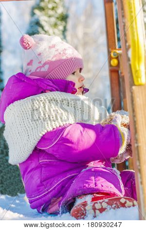 Little babe girl playing on the winter playground
