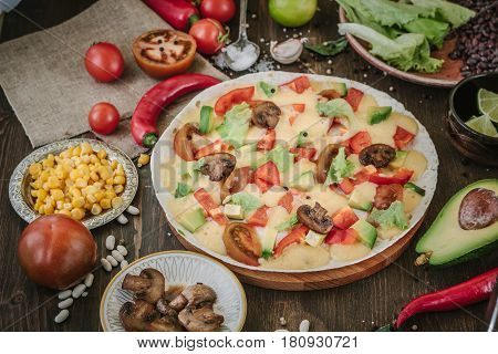 Vegetarian Home Made Pizza With Mushrooms And Vegetables Over Wooden Table, Surrounded By Ingredient