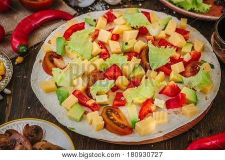 Tortilla With Salad Over It, Surrounded By Ingredients.