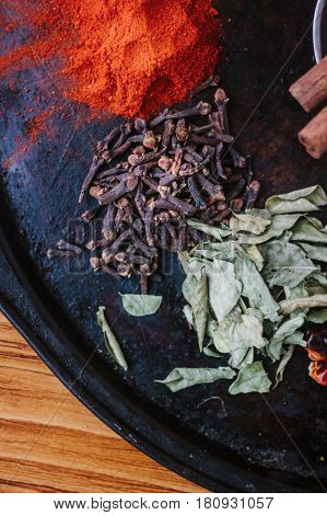 Black Cloves Spice Over Black Plate Surrounded By Spices.