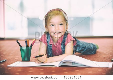 Blond hair girl lying on the carpet and plays with drawing n the children's playroom (vintage style)