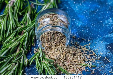 Branches Of Fresh Rosemary, Dried Rosemary In A Glass Jar On A Dark Blue Background