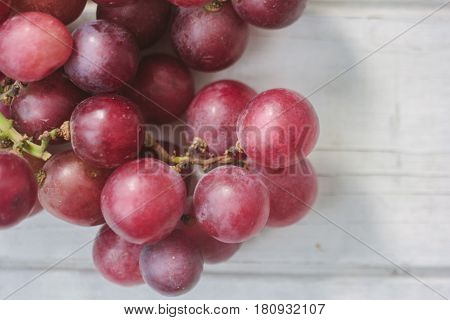 Red Grapes Over The White Wooden Board.