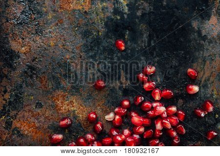 Border Made From Pomegranate Seeds Over Black Rustic Background.