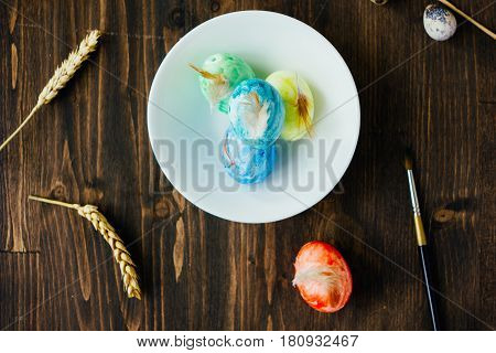 Red Color Egg Standing Near Ceramic Bowl Of Easter Eggs.