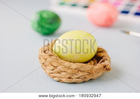 Yellow Color Egg In Small Nest Over Bright Background.